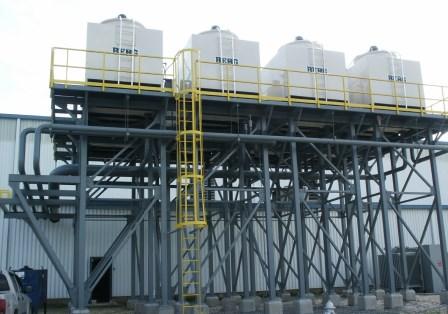 Bank of four fiberglass cooling towers on custom mezzanine with walkways.