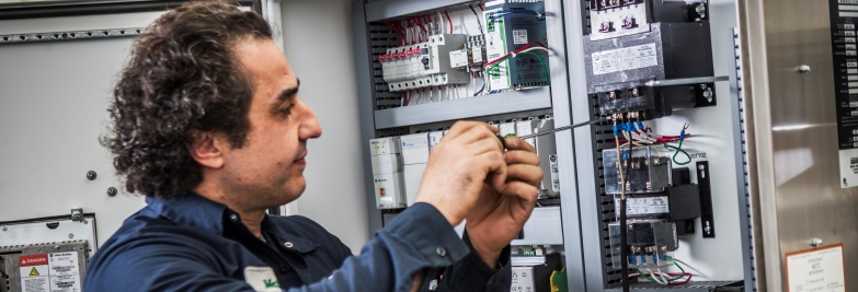 Berg service technician working on a refrigeration control panel.