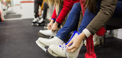 Women lacing skates up - how to reduce ice rink heating