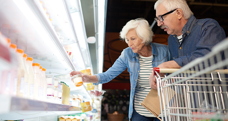 older couple looking into food and beverage chiller